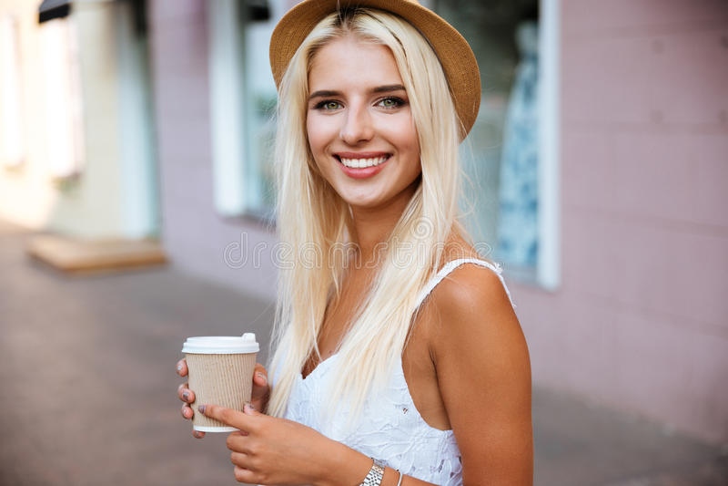 La fine su della ragazza nella tenuta del cappello porta via la tazza fotografie stock libere da diritti