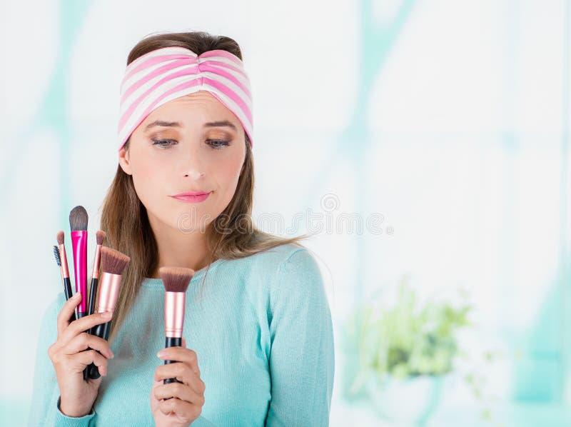 La fine su della tenuta felice della giovane donna in entrambe mani un insieme di compone le spazzole e l'uso in sua testa un ros fotografie stock