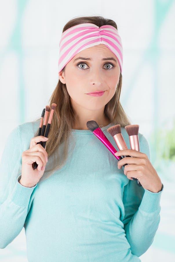 La fine su della tenuta felice della giovane donna in entrambe mani un insieme di compone le spazzole e l'uso in sua testa un ros fotografia stock libera da diritti