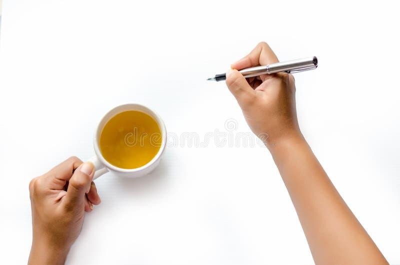 La fine su delle donne arma la scrittura con la penna metallica sulla mano bianca del fondo che tiene una penna su fondo bianco immagine stock libera da diritti