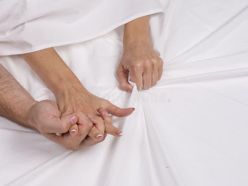 La fine su delle mani delle coppie si trova sul letto in camera da letto, gli amanti hanno il sesso intenso o fabbricazione l'org fotografia stock