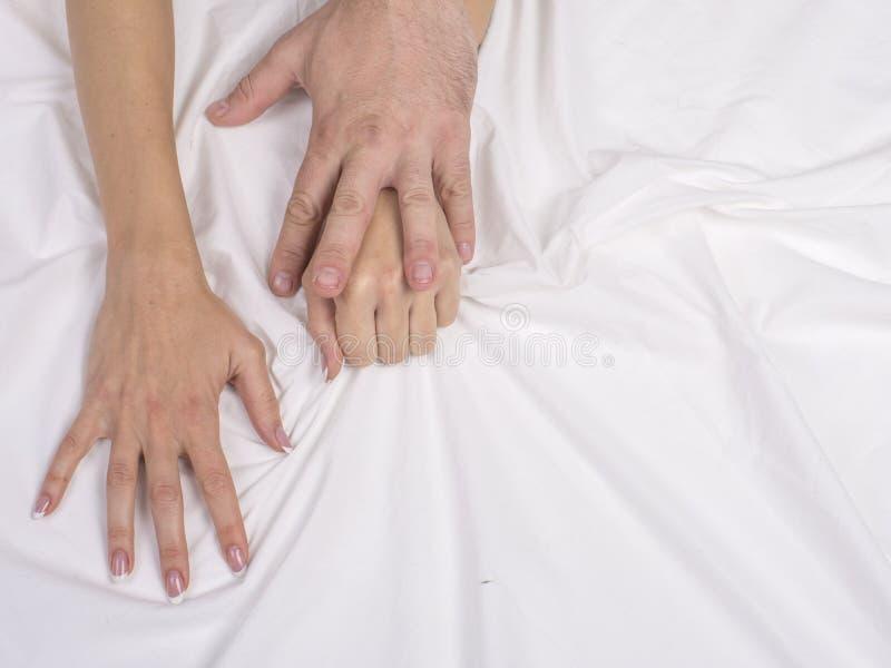 La fine su delle mani delle coppie si trova sul letto in camera da letto, gli amanti hanno il sesso intenso o fabbricazione l'org fotografia stock libera da diritti