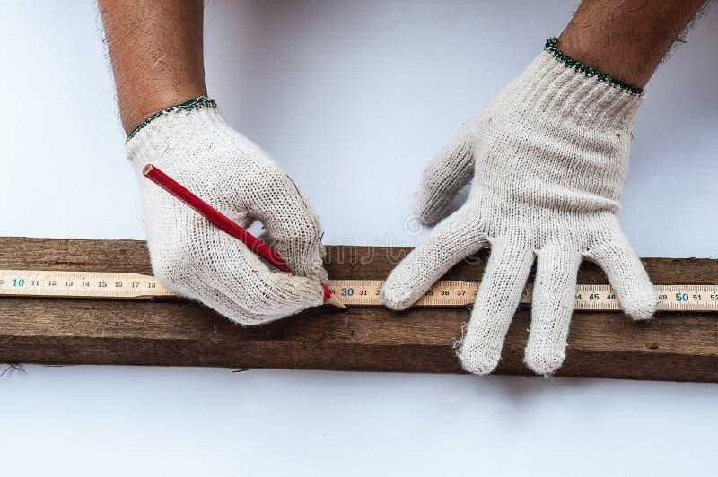 La fine su delle mani del carpentiere con il righello e il penceil preparano per il taglio di legno immagine stock