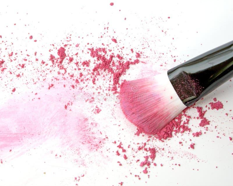 La fine su dello schiacciato di arrossisce su fondo bianco e sulla spazzola cosmetica immagine stock libera da diritti