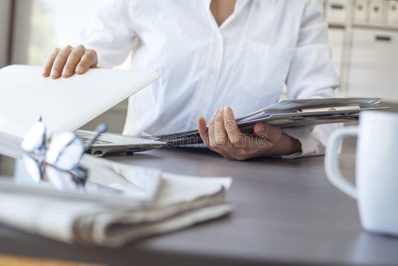 La fine su di una donna di affari passa lasciare il computer portatile di closing e del lavoro all'ufficio fotografie stock libere da diritti