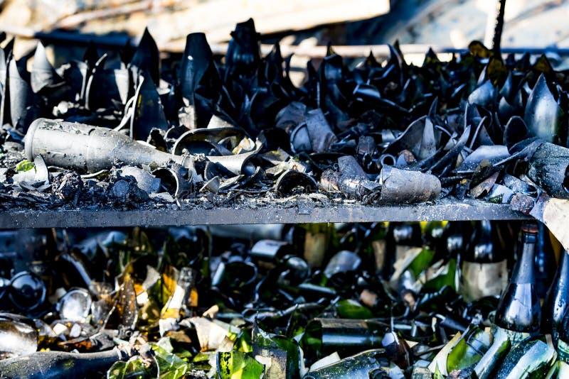 La fine su ha bruciato le rovine nocive delle bottiglie distrutte su assicurazione di ricerca di incendio doloso del supermercato fotografie stock