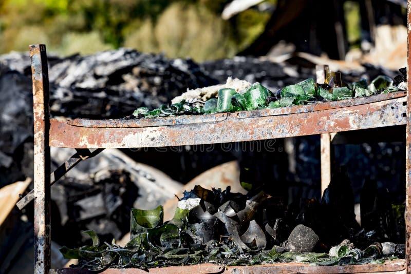 La fine su ha bruciato le rovine nocive delle bottiglie distrutte su assicurazione di ricerca di incendio doloso del supermercato fotografia stock