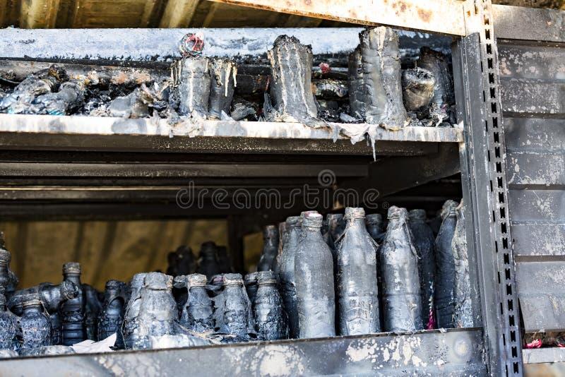 La fine su ha bruciato le rovine nocive delle bottiglie distrutte su assicurazione di ricerca di incendio doloso del supermercato immagini stock libere da diritti