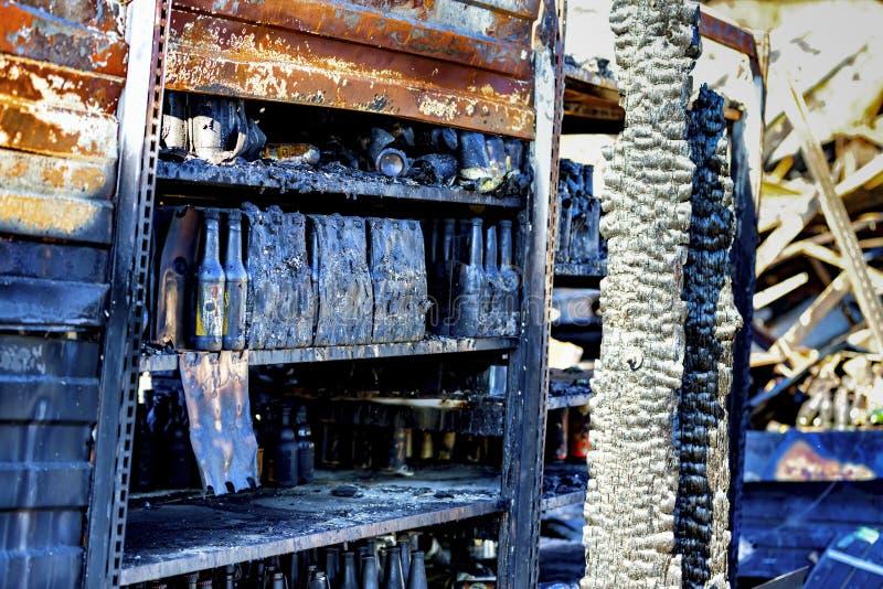 La fine su ha bruciato le rovine nocive delle bottiglie distrutte su assicurazione di ricerca di incendio doloso del supermercato immagine stock libera da diritti