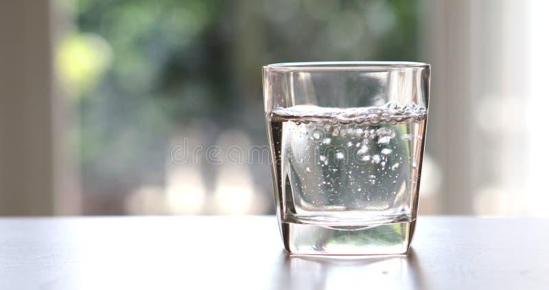 La fine su ha purificato l'acqua fresca della bevanda dalla bottiglia sulla Tabella I immagini stock