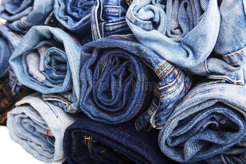 La fine su ha rotolato dei pantaloni delle blue jeans, pantaloni blu scuro del denim che mostrano la struttura su bianco immagini stock libere da diritti