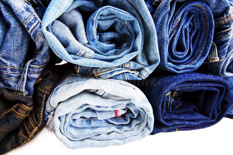 La fine su ha rotolato dei pantaloni delle blue jeans, pantaloni blu scuro del denim che mostrano la struttura su bianco fotografie stock