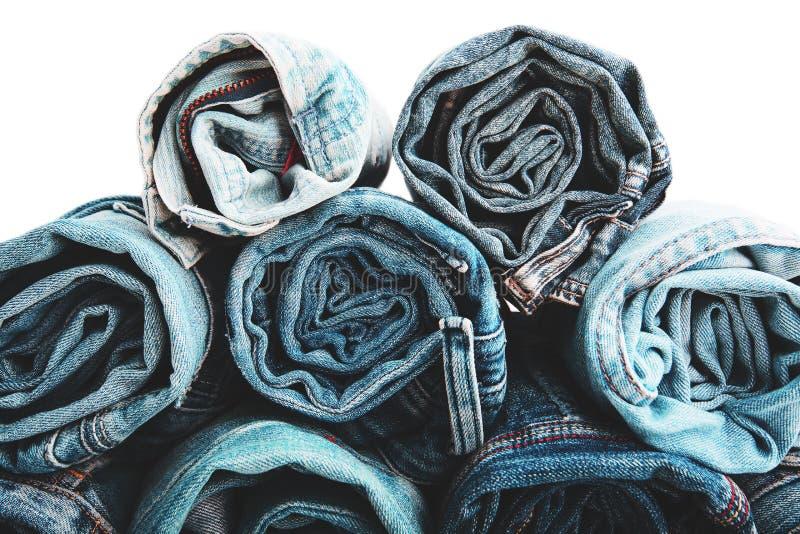 La fine su ha rotolato dei pantaloni delle blue jeans, pantaloni blu scuro del denim che mostrano la struttura su bianco immagine stock libera da diritti
