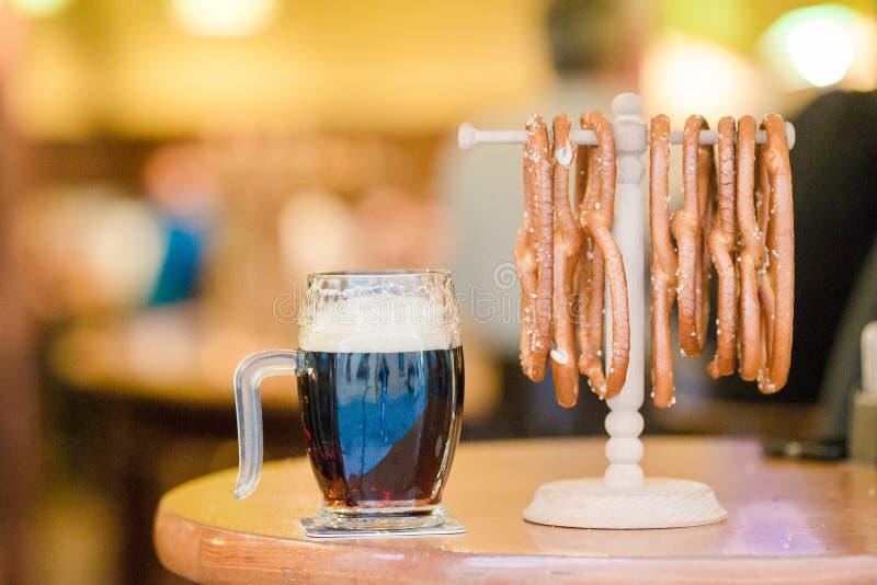 La fine su ha salato le ciambelline salate e la birra saporite su fondo di legno fotografia stock libera da diritti