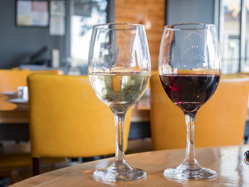 La fine su ha sparato di un vetro di vino rosso e di vino bianco fotografia stock