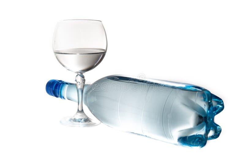 La fine su vetro da bottiglia ha purificato la bevanda dell'acqua dolce su fondo bianco fotografia stock libera da diritti