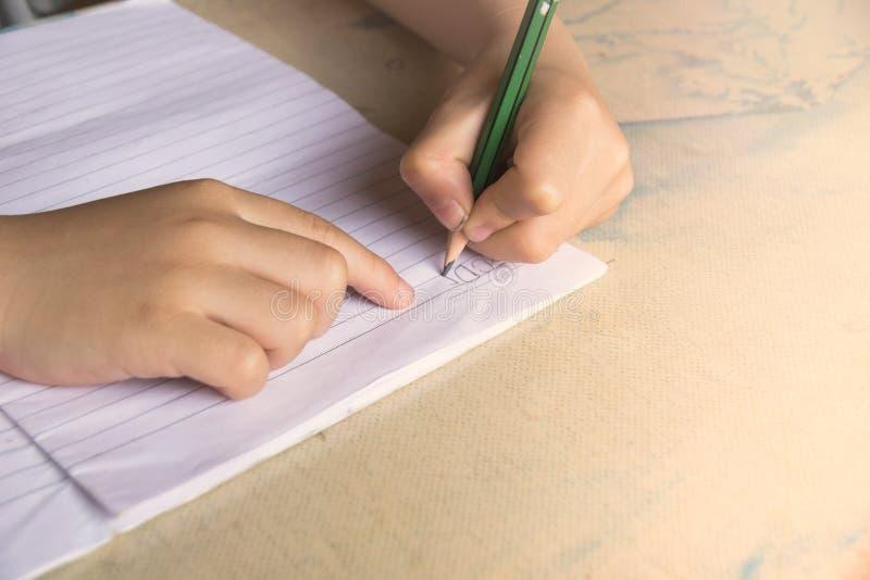 La fine sui bambini sta tenendo una matita e una scrittura immagine stock libera da diritti