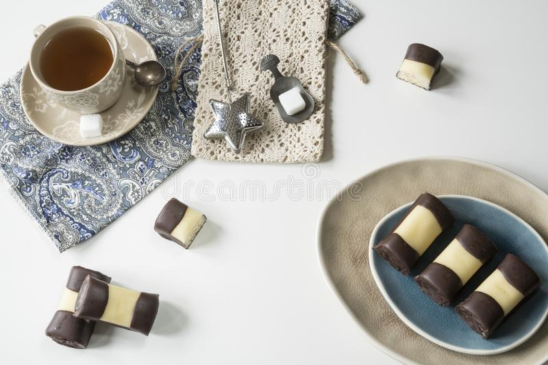 La fine sul biscotto olandese tipico del dolce con marzapane e cioccolato, ha chiamato il mergpijpje Tavola bianca, tazza di tè immagini stock libere da diritti