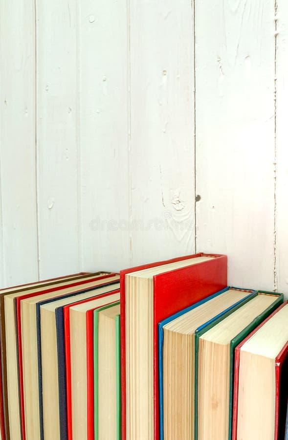 La fine sul libro novello rosso estende i precedenti è una parete di legno bianca fotografia stock libera da diritti