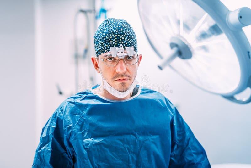 La fine sul ritratto del chirurgo plastico con chirurgico sfrega e lampade nella sala operatoria immagini stock