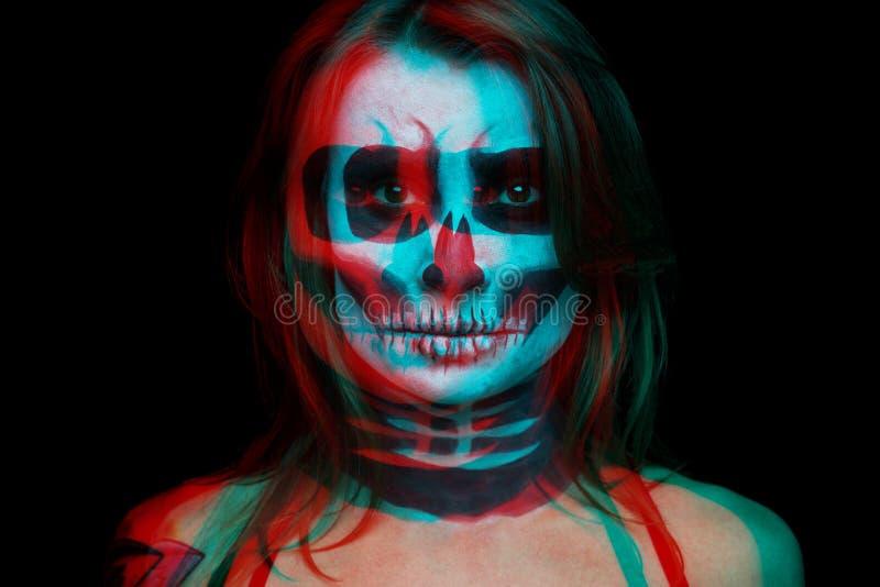 La fine sul ritratto della donna con il cranio di Halloween compone sopra fondo nero E fotografia stock