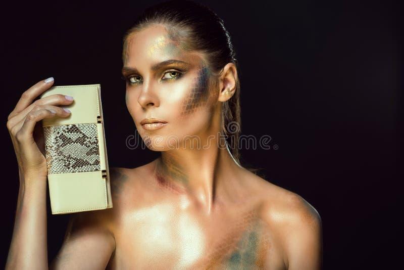 La fine sul ritratto della donna splendida con giallo osserva e lo snakeskin artistico compone la tenuta della borsa di cuoio bei immagini stock