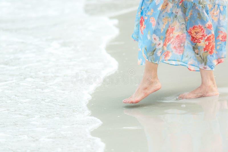 La fine sulla donna di stile di vita della gamba nella sensibilità lunga del vestito si rilassa e felice sulla spiaggia di sabbia fotografia stock