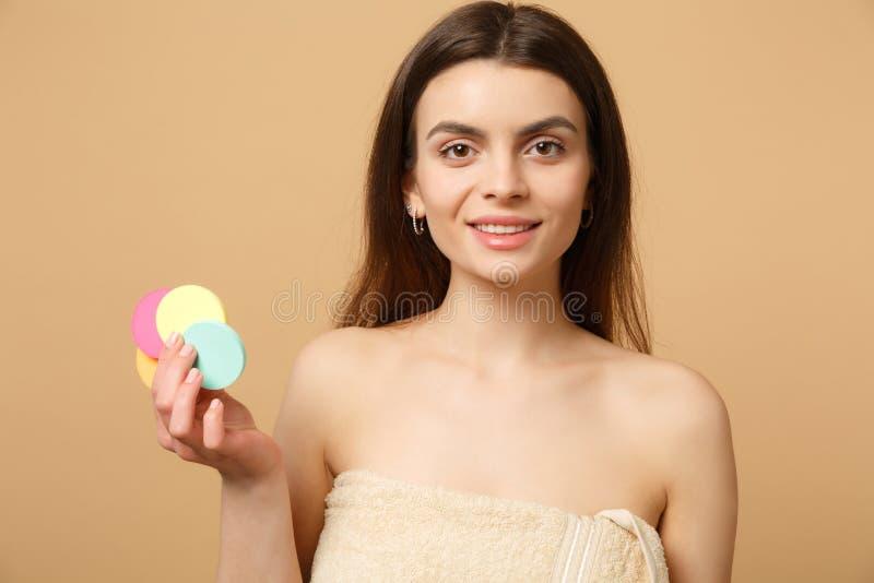 La fine sulla donna mezzo nuda castana 20s con pelle perfetta, rimuovente il nudo compone isolato sul fondo pastello beige della  fotografia stock