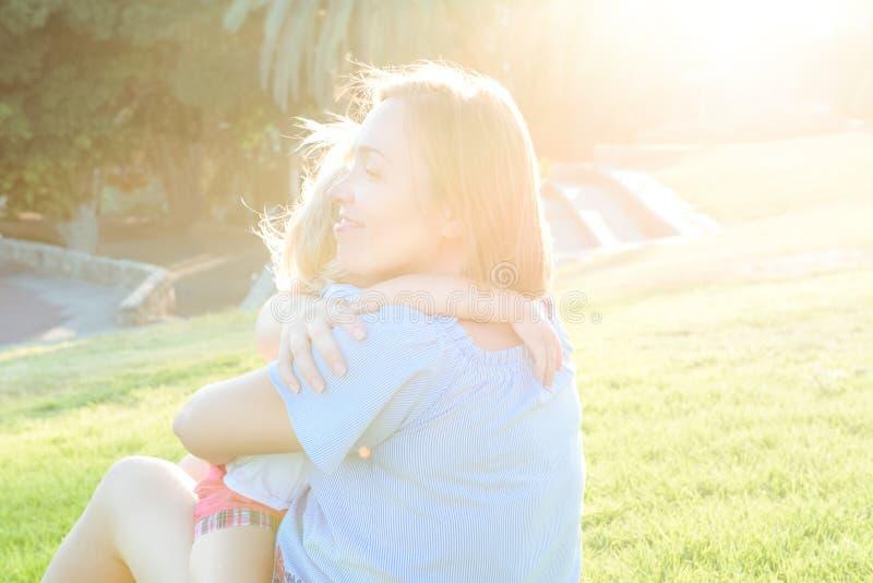 La fine sulla figlia del bambino del bambino e della madre che si rilassa, abbracciando, ridendo e si diverte sul prato dell'erba fotografia stock libera da diritti
