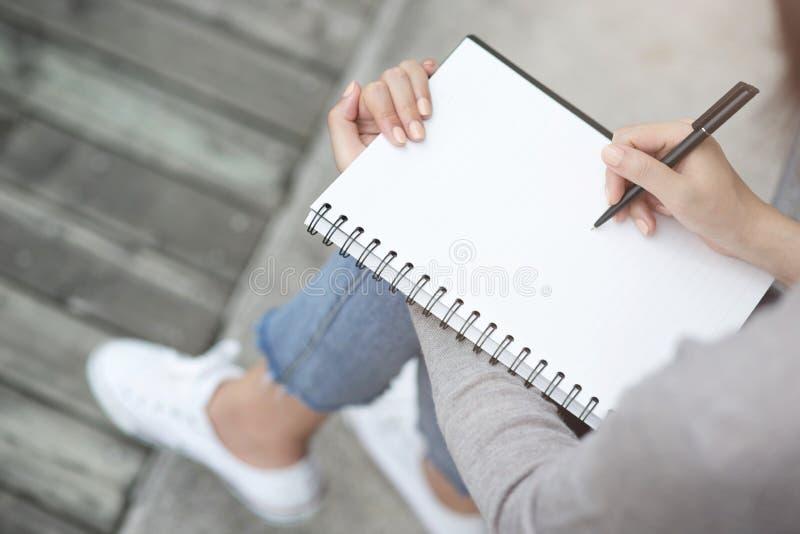La fine sulla giovane donna della mano sta sedendo su una sedia di marmo facendo uso della penna che scrive il blocco note record fotografia stock