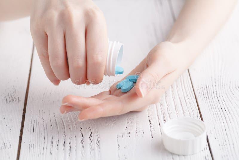 La fine sulla giovane donna versa le pillole dalla bottiglia Concetto di sanità e della medicina immagini stock libere da diritti