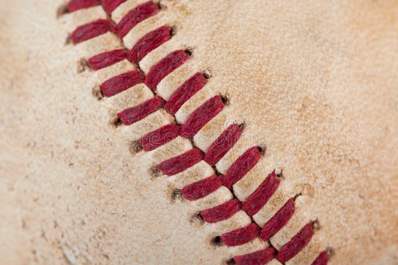 La fine sulla macro vista di rosso ha cucito le cuciture di un baseball consumato immagini stock libere da diritti