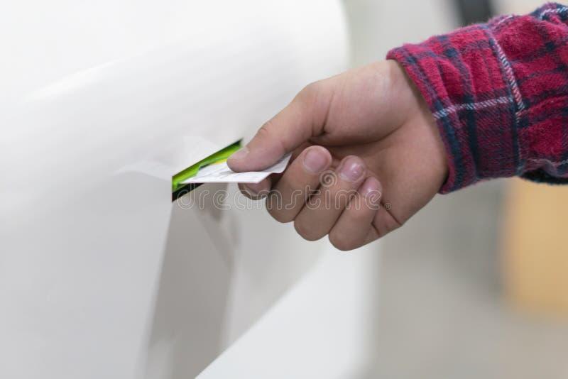 La fine sulla mano del cliente tira un numero del biglietto dalla macchina dell'erogatore per aspettare in coda in ufficio postal fotografia stock libera da diritti