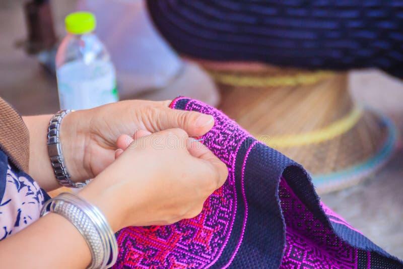 La fine sulla mano della donna di Hmong sta cucendo tribale tradizionale copre immagini stock libere da diritti