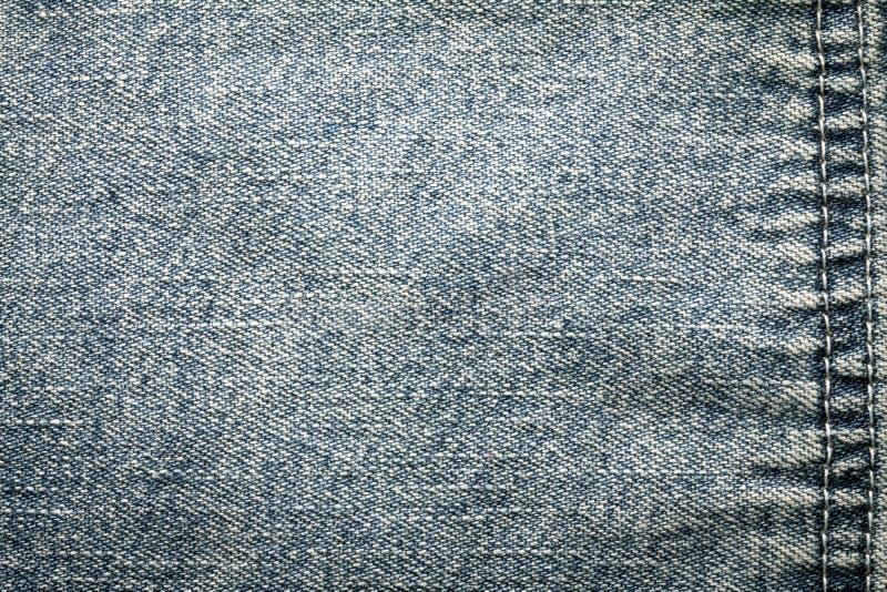 La fine sulle blue jeans del denim sorge con struttura della cucitura fotografie stock