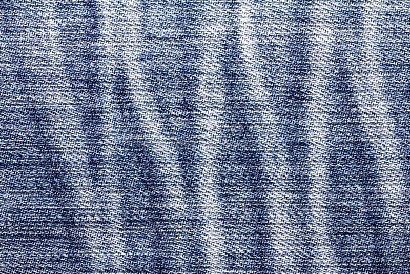 La fine sulle blue jeans luminose del denim sorge con il te dello zoccolo dello straccio fotografia stock libera da diritti