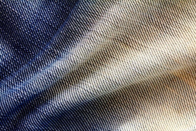 La fine sulle blue jeans luminose del denim sorge con la parte posteriore di struttura dell'onda fotografia stock libera da diritti