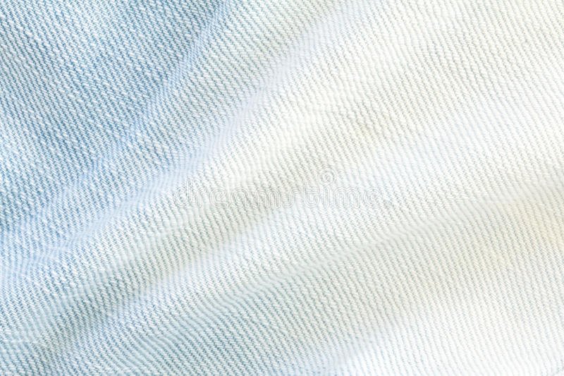 La fine sulle blue jeans luminose del denim sorge con la parte posteriore di struttura dell'onda fotografia stock