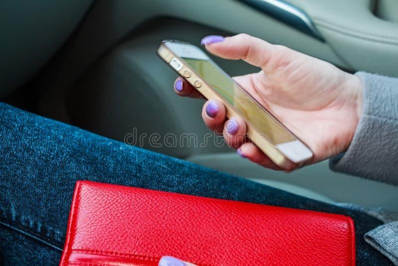 La fine sulle mani del ` s della donna tiene lo smartphone fotografia stock libera da diritti