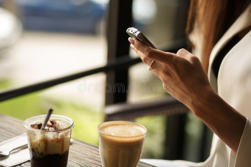La fine sulle mani della donna sta chiacchierando nel telefono mentre si sedeva in un caffè con una tazza di caffè e un dessert fotografia stock
