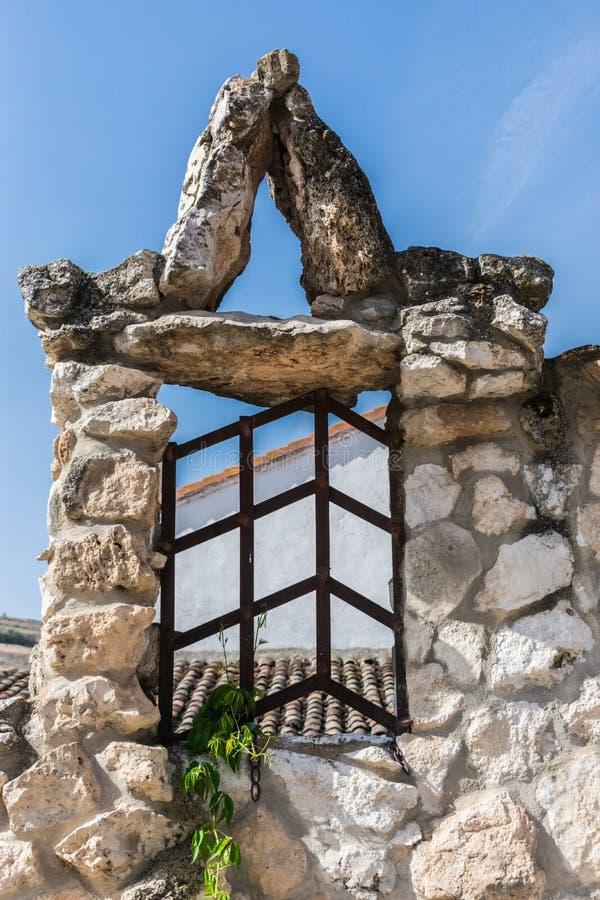 La finestra con ferro recinta la casa di pietra immagine stock libera da diritti
