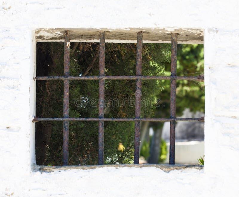La finestra con le sbarre di ferro sulla parete bianca immagini stock