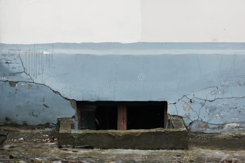 la finestra con vetro rotto in un seminterrato in una vecchia casa ha distrutto il gray ed il beige dello stucco immagine stock