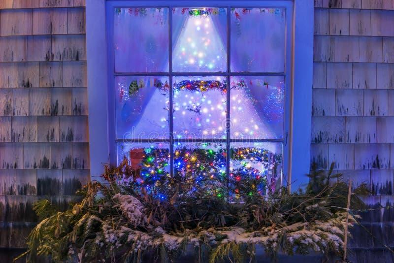 La finestra di notte con i modelli gelidi ed il Natale multicolore luminoso Luci del ` s del nuovo anno immagini stock libere da diritti