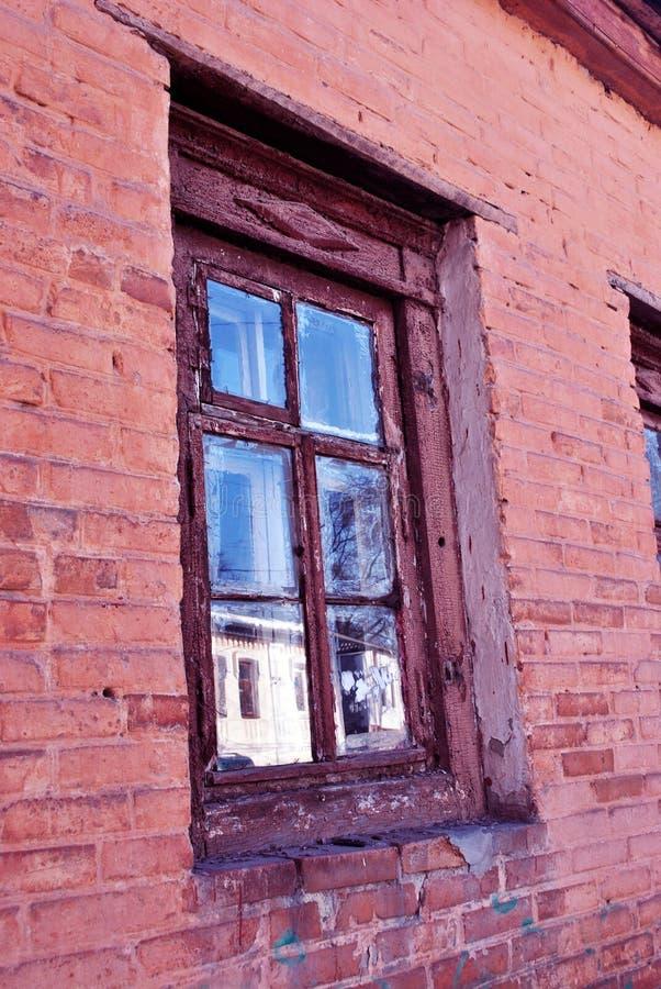 La finestra di vecchia costruzione di mattone rosso, riflessione della via di inverno, fondo fotografia stock libera da diritti