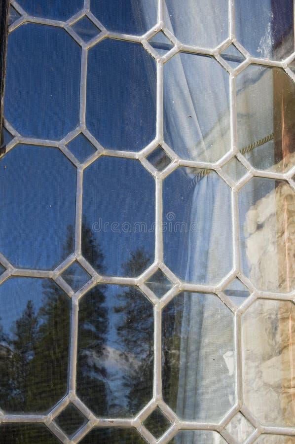 La finestra di vetro al piombo riflette il cielo blu e gli alberi immagini stock