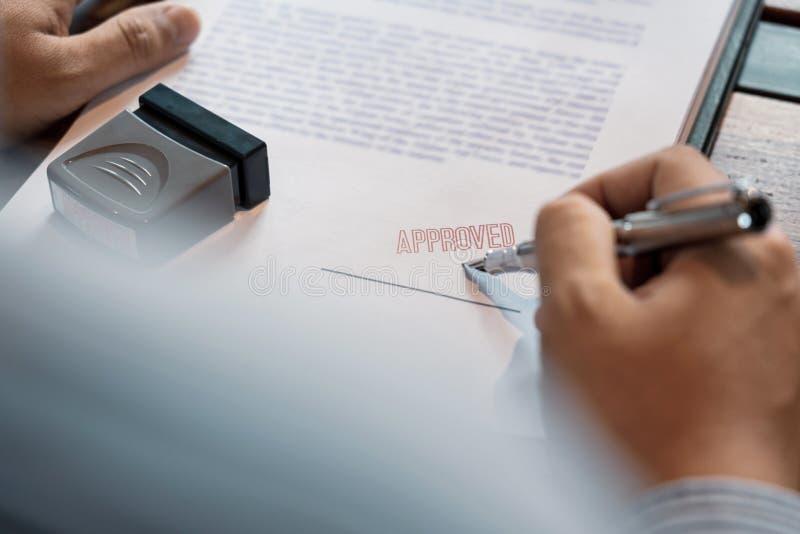 La firma mettente o di firma di affari della mano maschio senior dell'uomo nel contratto del certificato dopo approva il bollo su fotografia stock