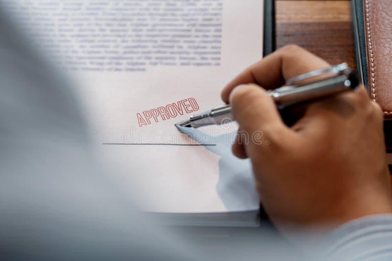 La firma mettente o di firma di affari della mano maschio senior dell'uomo nel contratto del certificato dopo approva il bollo su immagini stock libere da diritti