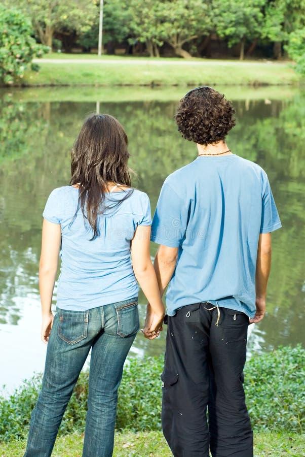La fixation de couples remet faire face à un étang - verticale photos libres de droits