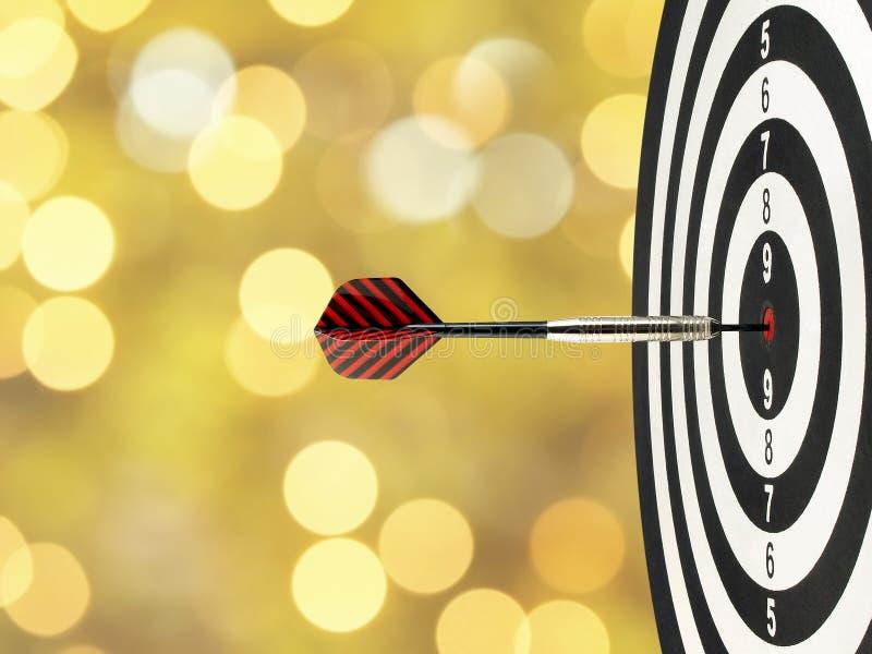 La flèche en gros plan de dard frappant au centre de cible sur la boudine dans la cible en bois avec de l'or jaune brouillé allum images stock
